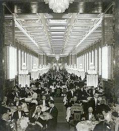 Transatlántico Normandie, gran comedor de primera clase decorado con muebles de Ruhlmann y paneles fiurativos de Jean Dunand. Las lámparas asemejan columnas de agua o surtidores, muy a juego con los vestidos drapeados de las damas, pero también fustes de columnas dóricas.