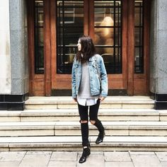 Grungy in ripped black jeans and an over-sized denim jacket.