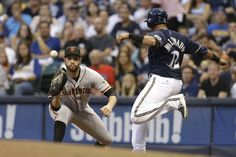 MILWAUKEE, WI - AUGUST 06: Martin Maldonado #12 of the Milwaukee Brewers beats the throw to Brandon Belt #9 of the San Francisco Giants at first base during the bottom of the second inning at Miller Park on August 06, 2014 in Milwaukee, Wisconsin. (Photo by Mike McGinnis/Getty Images)