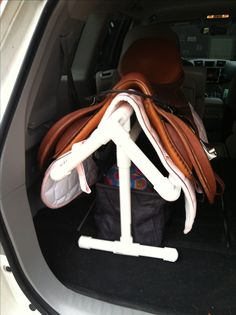 PVC pipe saddle rack for back of car. Bag underneath to hold helmet, gloves, half chaps and bridle. Perfect for keeping stuff organized. I see a project for the hubby.