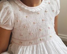 Gorgeous white hand smock dress with pale pink hand embroidery This gorgeous baby dress is made out of cotton spot white fabric which is perfect for a christening or a special function. Hand smocked bodice is fully lined and adorned with Smocking Baby, Smocking Patterns, Smocking Plates, Girls Smocked Dresses, Little Girl Dresses, Smocked Baby Clothes, Vintage Girls Dresses, Toddler Girl Dresses, White Baby Dress