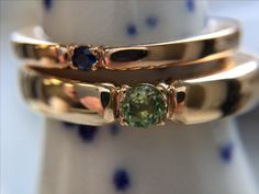 """""""One of a kind"""" the stone decides size of your ring. Here's a rosegold band with a blue saphire and a redgold ring with a peridote."""