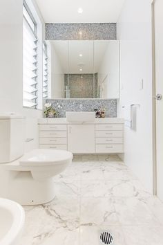 White bathroom with square basin, marble floor tiles, mosaic splashback tiles and large mirror. Cobden & Hayson Sydney Real Estate