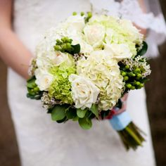 Katharine and Mike: Katharine's soft bouquet reflected their color palette with green Hypericum berries, white roses, and green and white hydrangea. Image Credit: Maria Linz Photography