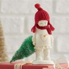 "Handcrafted snowbaby in porcelain bisque with knit hat and sisal tree. 3"" w x 5 1/2"" h x 4 3/4"" d."