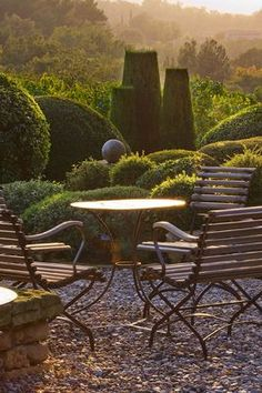 PROVENCE, FRANCE: GARDEN OF NICOLE DE VESIAN, LA LOUVE: GRAVEL TERRACE BESIDE THE HOUSE AT DAWN WITH METAL TABLE AND CHAIRS AND CLIPPED TOPIARY SHAPES