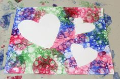 Scoop coloured soap bubbles onto paper topped with paper heart cutouts. Let bubbles pop.