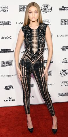 Gigi Hadid traded the runway for the red carpet and caused quite a commotion at the Sports Illustrated Swimsuit Issue Event in what might be the sexiest jumpsuit ever—a black bead-embroidered sheer Julien Macdonald one-piece that she styled with black Kurt Geiger pumps.