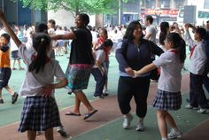 Wharton MBA students dancing with local elementary students during a visit to a local school in Chengdu