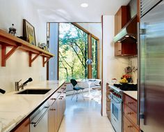 To brighten the kitchen, which was once the darkest room, Watson and Tschopp decided on a glossy white finish, painted directly on the same rough-cut cedar paneling used throughout the house. This maintains the consistency of materials and texture, while Cedar Paneling, Cedar Walls, Kitchen Decor, Kitchen Design, Kitchen Ideas, Kitchen Living, Nice Kitchen, Pantry Ideas, Open Kitchen