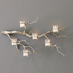 don't remember where this was from, but you can make by painting branch with your colors, wrap candles with wire, add picture hangers to back - making sure to level