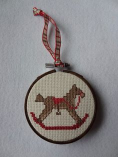 this hand made ornament pictures a vintage rocking horse it is cross stitched on aida