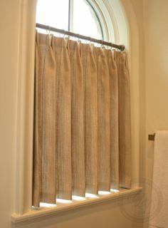 Cortina con barra en ventana en forma de arco.