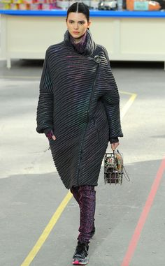 Kendall Jenner rocks the Chanel runway, donning a purple metallic ensemble and carrying a shopping basket-style purse.