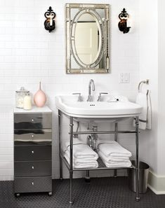 After: Basement Bathroom    White tiles brighten a small bathroom.      Iron sconces and a Moroccan mirror add edge to the clean-lined basement bathroom. A reflective drawer unit and chrome fixtures give the illusion of a bright, sparkling room.