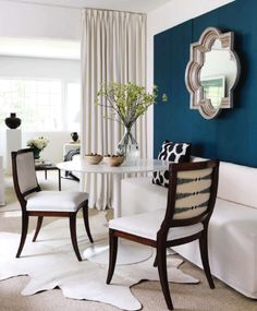 The warm browns on the chair and the White backdrop is the perfect place to put any accents. This teal wall gives the room a more cool feelings witch balances out the room. reminds me of carries apartment in a weird kind of way