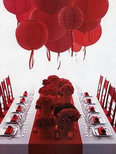 red wedding table centerpieces, but add yellow roses, yellow vases, yellow candle holders, and yellow lanterns