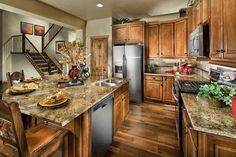 The open layout of the kitchen in the Connemara model in Granby Ranch, Colorado is the perfect place for entertaining with friends and family. Complete with hardwood flooring, artisan maple cabinetry with bronze hardware, gold granite slab countertops, and stainless steel appliances with gas range.