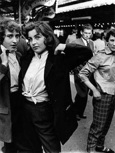 U.K. Teddy Girls, 1950s. Like Teddy Boys, their male counterparts, these young women were primarily, maybe entirely, working class. Many dropped out of school at 14 or 15 to work as shop assistants, secretaries or assembly line workers. Others may have gone onto art college; Mr. Russell learned of this subculture through a friend at Southwest Essex Polytechnic and School of Art, where he was studying photography (from http://www.enjoy-your-style.com)