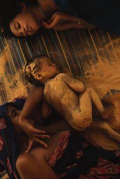 um bebê de oito meses de idade, coberto de tempestades de areia do leito de um lago seco, cochilos ao longo do lado sua mãe e irmã no Mali. foto joanna b. Pinneo. 1997