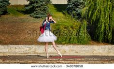 Girl listening to music on headphones. Cute ballerina dancing hipster in autumn park. A girl wearing a tutu and sneakers, sunglasses. Girl dancing ballet pas on tiptoe. The concept of youth fashion.
