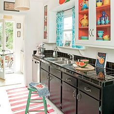 This colorful kitchen sports two-toned cabinets with a pop of bright color on the interior.