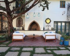 Spanish Style Design- Moorish arch shaped fireplace, blue glass pendant lights hang from the tree; tile seating area; Blue accent colors