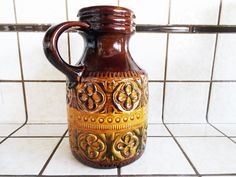 It is a 60s vintage pattern pitcher. With gold and brown color and flower-ish style, it shows very traditional style. You can use with red wine, white wine or cocktail when you have a party in your mid-century house. When you taste the drinks with this vintage pitcher, it will definitely different and delicious. In the bottom, it shows the series number:489-25 and made in West Germany to prove that it is a mid-century product.