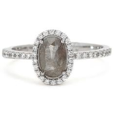 One-of-a-kind Fourteen Karat(14K) white gold ring featuring a fancy oval cut natural grey diamond that is accented with round brilliant cut diamonds. If you are looking for an alternative engagement ring this is a great option! Price listed is complete.