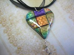 Pieced Polymer Clay heart pendant by Guadalupe Meter   This polymer clay pendant was made using Lumiere paints (Halo Jewel) on silver colored clay. For texture, I used a scrap piece of tulle (honeycomb).