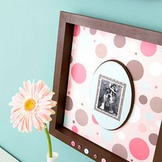 Scrapbook paper as a mat for a personal snapshot. The frame is adorned with glued on buttons to keep the circle theme. Via BHG.com