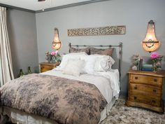 The new master bedroom is done in soft gray with warming wood tones, ornamental sconces and a few colorful accents.