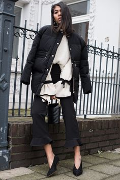 storm wears mango sweater in white with stella mccartney bag with gold detail and black puffer jacket and mango pants and celine pumps
