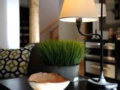 A three-tiered side table serves up a container of fresh grass and decorative bowl, fashioned from a fallen tree.