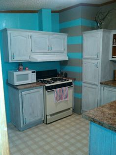 Remodelling on a budget only paint.  Old brown cupboards distressed white, grey and teal stripes