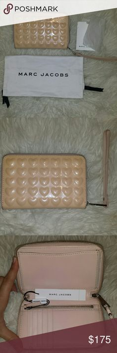 Marc Jacobs patented leather wristlet and dust bag Marc Jacobs patented leather wristlet and dust bag: brand new with tags! Color: Seashell Peach Style number: M7000076 Original care slip included.  Exterior: patented leather hearts and Marc Jacobs New York logo Interior left side: 6 card slots. Two full length receipt slots. Zippered coin slot Interior right side: Cell phone slot big enough for iPhone 6 and fits my Galaxy s4 as well with a little room to spare. Suggested retail price: 175…