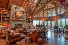Astonishing Log Cabin Homes Interior: Enchanting Large Log Cabin Homes Interior Designs Unique Antler Chandeliers Wood Flooring Natural Stone Wall Fireplace Brown Leather Sofas Wall Bookshelves Glass Walls Large Window Round Small Dining Table ~ dropddesign.com Interior Design Inspiration: