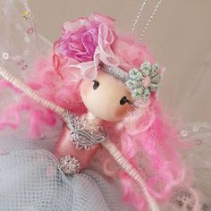 Meet Little Miss Evelyn, a beautifully handcrafted fairy doll that will adorn any room in your home! She is approximately 7 inches tall from the tip of her toes to the top of her head and hangs from a silver thread. She is wearing a pretty, layered pale mint/grey tulle dress with a