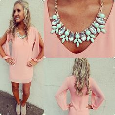 Peach colored dress with statement necklace.