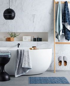 White round freestanding bathroom, matte black tap and mixer, timber towel rack, marbled feature wall. #taps #interiordesign #bathroom #australia #architecture #bathroomdesign #bathroomcollective Visit our website for more www.bathroomcollective.com.au