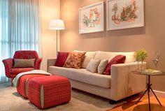 """""""Inspirada em um projeto assinado pela arquiteta Daniela Berardinelli, monte uma sala de estar com sofá, tapete e dois pufes na cor vermelha."""" Casa"""