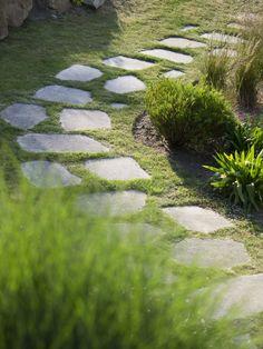 Une allée de pas japonais permet de déambuler dans le jardin, entre massifs et rocailles. Il s'agit de pierres de Languédias (les mêmes qui servent à retenir la terre dans les massifs de rocaille) : elles ont été sciées, puis cassées en dalles pour composer ce chemin. En jointure, selon les endroits, on trouve soit du gazon, soit un mélange de plantes couvrantes fleuries (Frankenia laevis, Soleirolia soleirolii et Phyla canenscens).