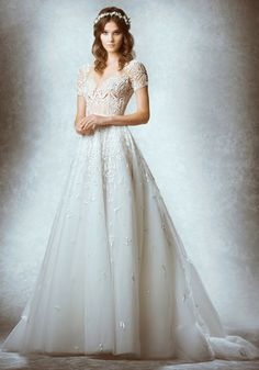 ZUHAIR MURAD Illusion Neckline A-Line Wedding Dress in Tulle An illusion neckline wedding dress in A-line silhouette with delicate beadwork and sequins embroidery on the bodice cascading to the skirt, featuring a sheer bodice with short sleeves and open V-back detailing.