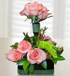 A year ago 1800Flowers asked me to come up with some designs. This is one of them. Their product code 105095. Their price $84.99.A dozen pink roses ( rose color is your choice) designed topiary style surrounded by flax leaves