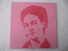 Auf der 25x25cm großen Leinwand seht ihr ein Portrait der mexikanischen Malerin Frida Kahlo. Das Portrait zeigt die Malerin in pinken Farben vor einem