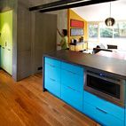 Modern Kitchen Renovation with Mid-Century Roots A dark concrete counter and blue laminate cabinets surround the Jenn-Air microwave drawer in architect Janet Bloomberg's kitchen. The pendant hanging above the table is a Tejido Round Suspension from Artemide. Photo by: Greg Powers
