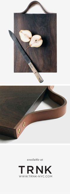 A handcrafted walnut serving board with a saddle leather handle.: