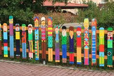 I want this fence..great idea, Students could paint themselves on yard sticks. Yard sticks are cheap. It's so bright and colorful and would be lots of fun to create!