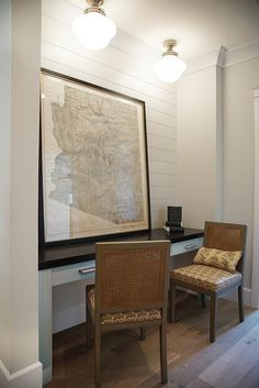 A framed map leans against a white shiplap wall as it sits on a white built in desk topped with a black desk top seating two can back desk chairs illuminated by two schoolhouse semi flush mount lights.