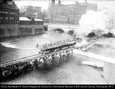 Working on the Genesee River, c.1915.  Picture shows the Erie Canal Aqueduct, which later became the broad street bridge.  The building to the left was the Kimball Tobacco Company.  The Blue Cross Arena is now located on that site.